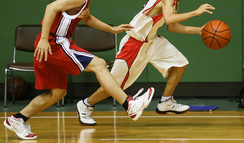 バスケットボールで競い合う2人